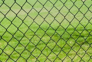 Chain link fence against grass. What is a chain-link fence made of?