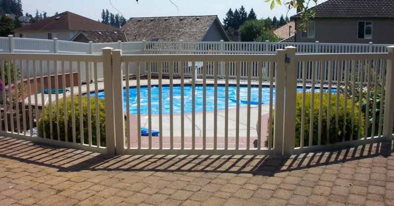 Compare chain link wood and vinyl fences. A vinyl fence surrounds a swimming pool.