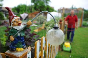 A garden gnome atop a picket fence.