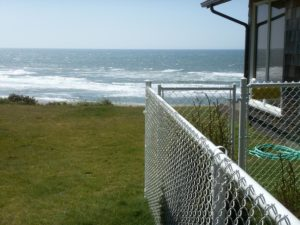 A chain link fence is seen at an ocean-front property.