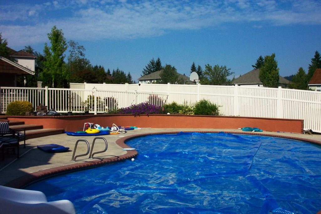 White vinyl fence behind a swimming pool