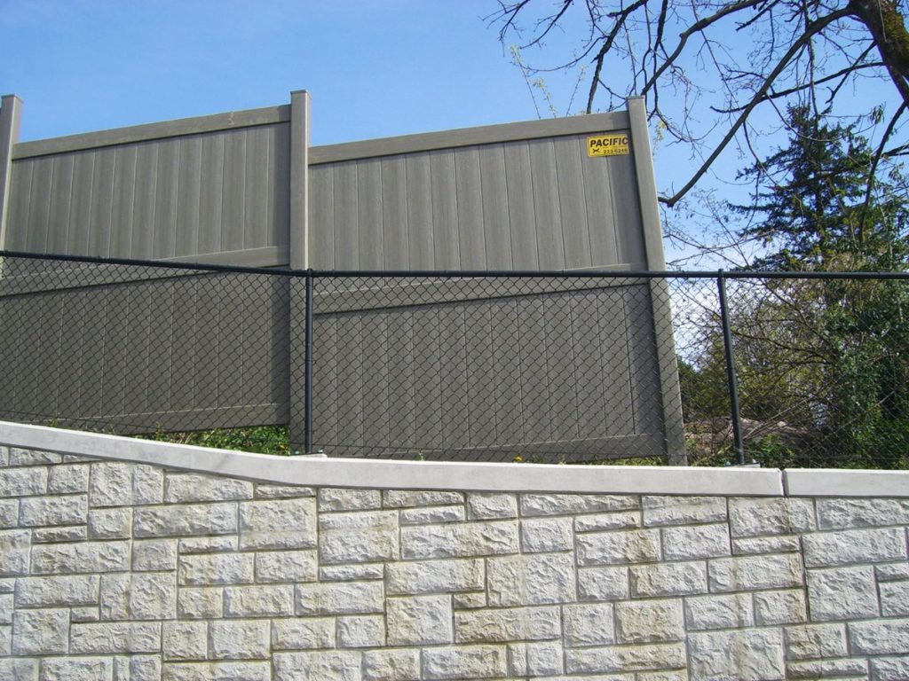 Vinyl fence on a retaining wall
