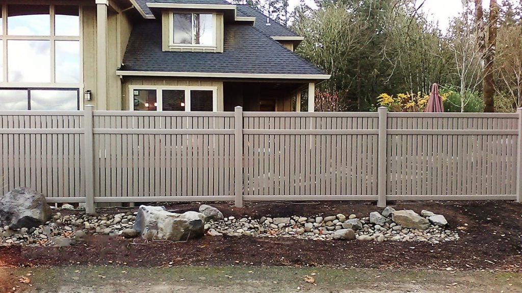 Brown vinyl fence in front of a home